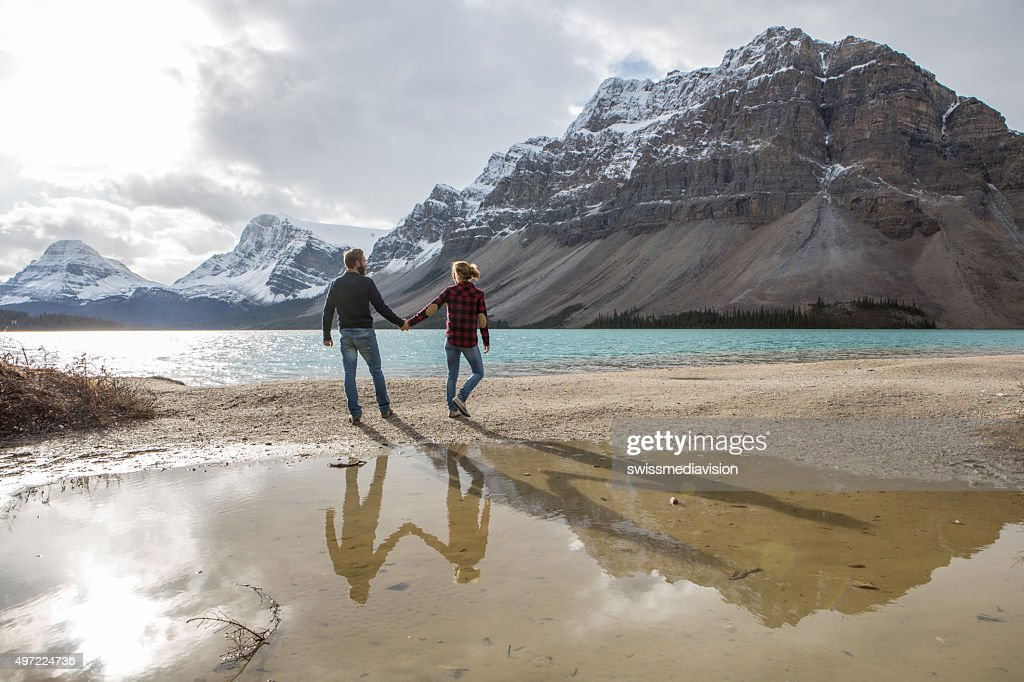 Cheerful young couple holding hands by the lake
