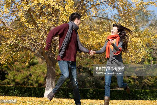Cheerful young couple in love running on the lawn in autumn