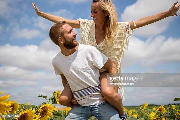 Alegre jovem Casal no meio de um campo de girassol