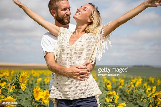 Cheerful young couple in the middle of a sunflower field