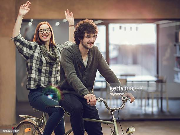Cheerful young couple on a tandem bicycle indoors.
