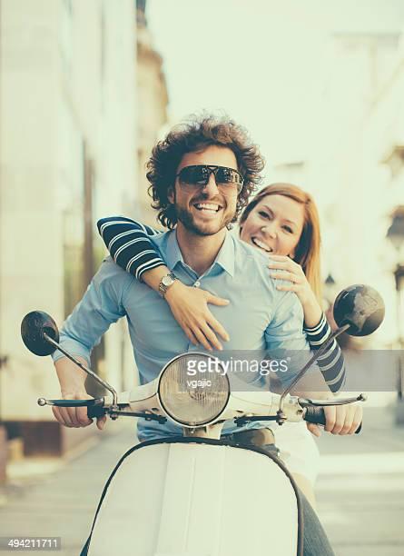 Allegro giovane coppia equitazione su una motocicletta.
