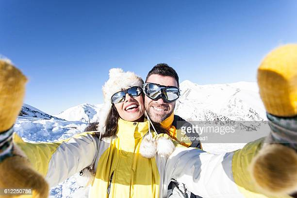 Cheerful young couple skiers making selfie in the snow mountain