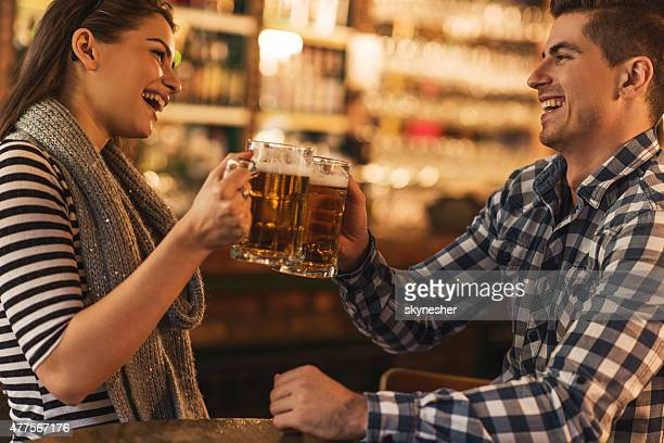 Cheerful young couple toasting with beer in a bar.
