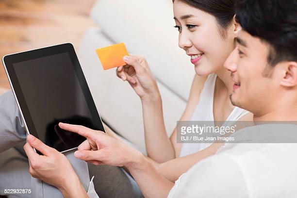 Cheerful young couple using a digital tablet shopping online