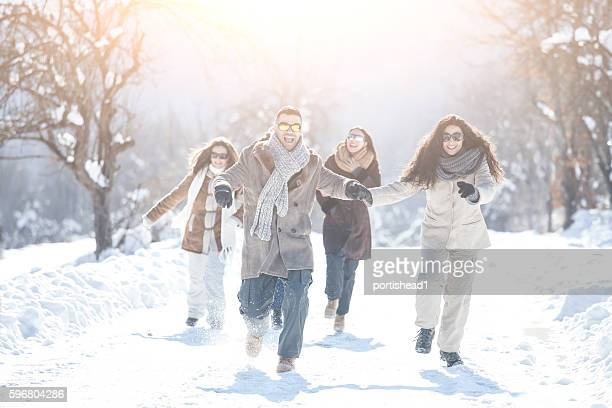 Cheerful young couples running on snow path