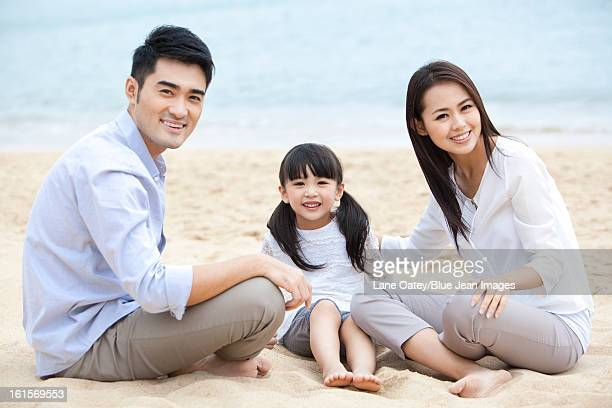 Cheerful young family sitting on the beach of Repulse Bay, Hong Kong