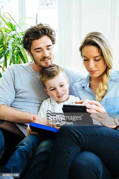 Cheerful Young Family Using Technology Together In The Living Room