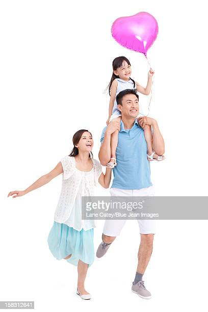 Cheerful young family with a heart-shaped balloon