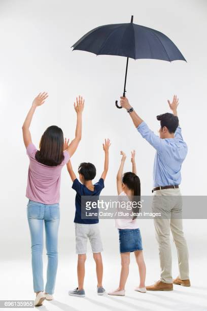 Cheerful young family with an umbrella