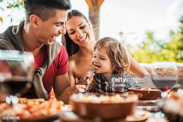 Cheerful young father feeding his son in restaurant.