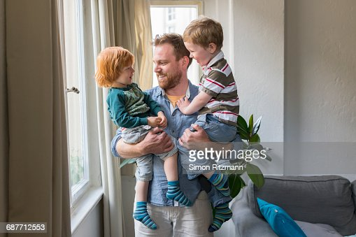 Cheerful young father holding two toddler boys