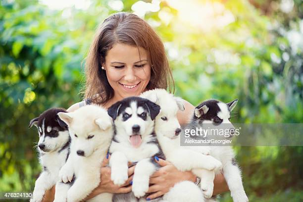 Cheerful Young Female Holding Five Lovely Husky Baby Puppies