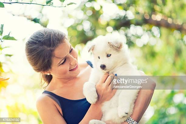 Alegre joven, que abrazan su adorable bebé cachorro Husky