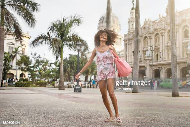 Cheerful young female is dancing against Capitolio