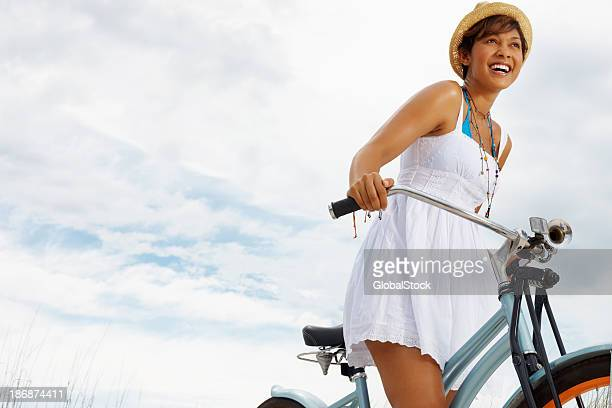 Cheerful, young female riding bicycle against cloudy sky