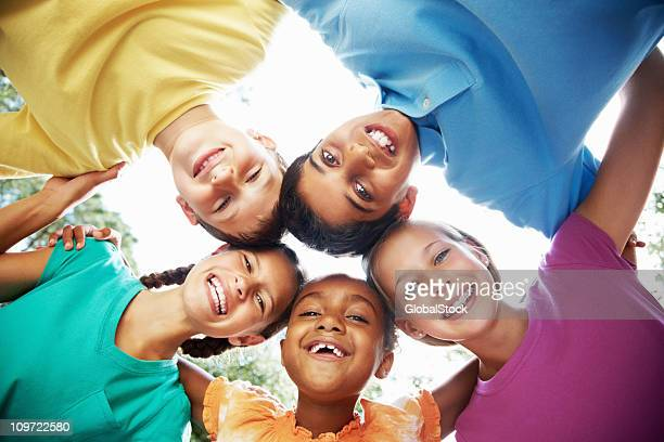 Cheerful young friends having fun against sky