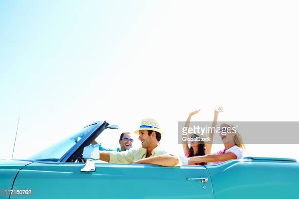 Cheerful young friends in a car on vacation trip