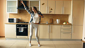 Cheerful young funny woman dancing and singing with ladle while having leisure time in the kitchen at home in the morining