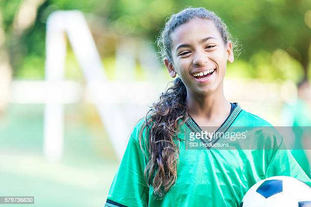 Cheerful young girl outside with a soccer ball