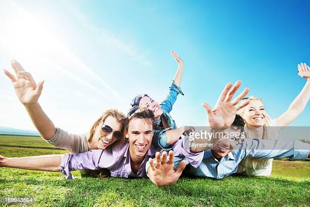 Joyeux groupe de jeunes gens allongé dans la nature.