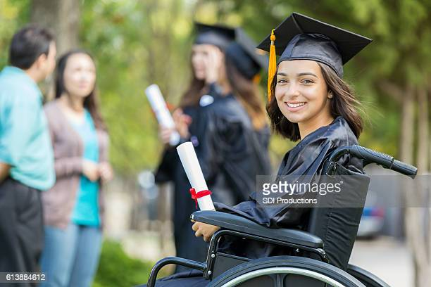 Cheerful young Hispanic woman holds college diploma