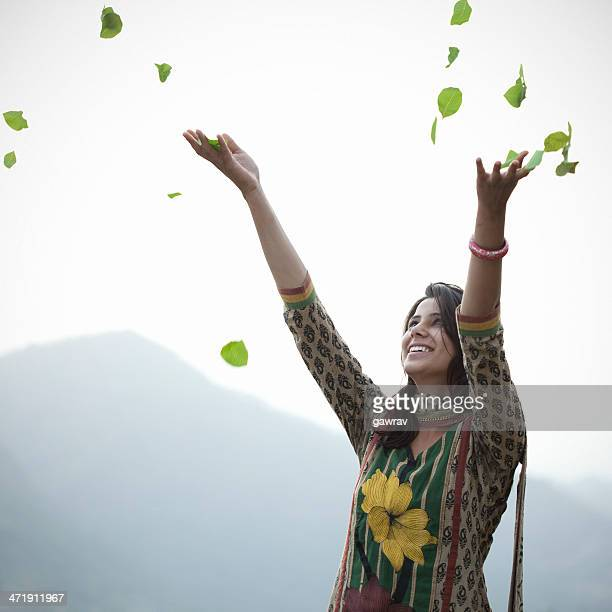 Fröhlich junge indische Frau werfen Blätter in der Luft