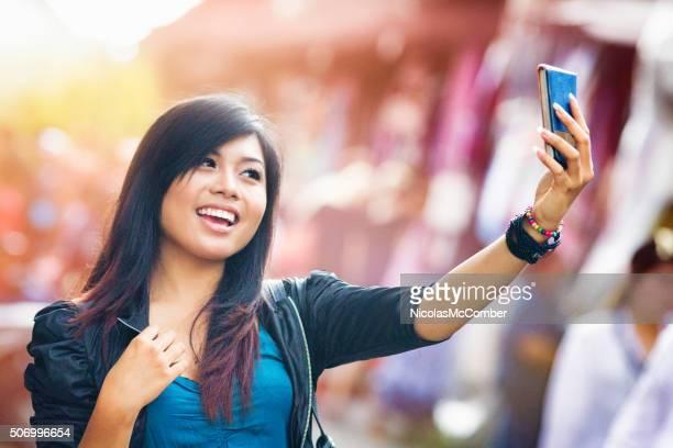 Fröhliche junge Frau ein selfie Fotografieren indonesische