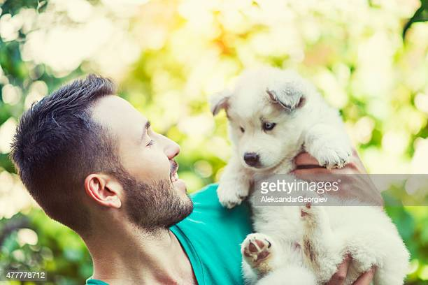 Cheerful Young Male Hugging his Lovely Husky Baby Puppy