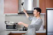 Cheerful young man cooking in kitchen