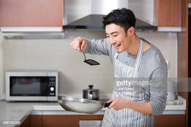Cheerful young man doing taste test in kitchen