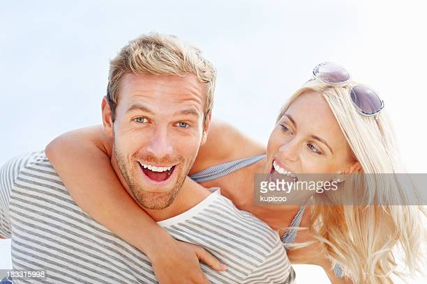 Cheerful young man giving his pretty girlfriend a piggybackride