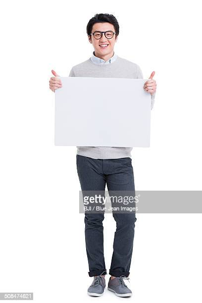 Cheerful young man holding whiteboard