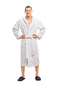 Full length portrait of a cheerful young man in a white bathrobe isolated on white background