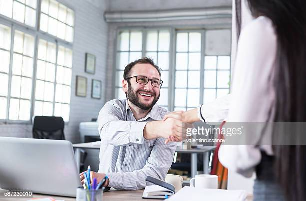 Cheerful young man in handshake at workplace