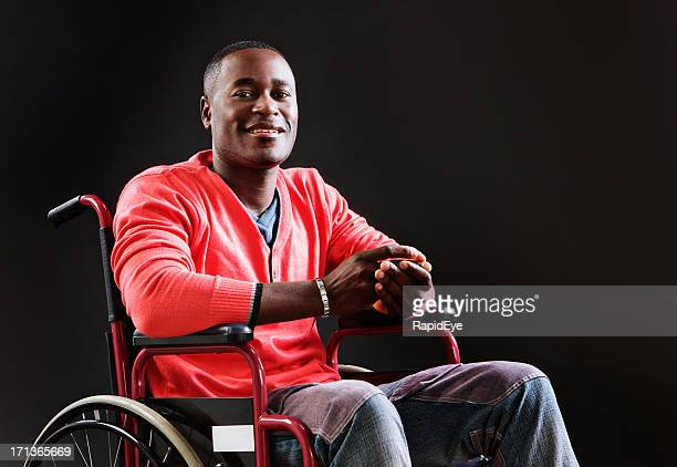 Cheerful young man in wheelchair, perhaps an injured athlete recovering