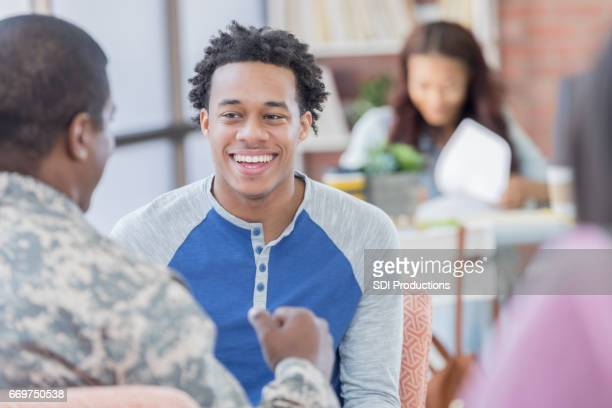Cheerful young man meets with armed forces enlistment officer