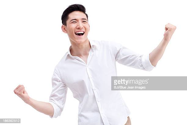 Cheerful young man punching the air