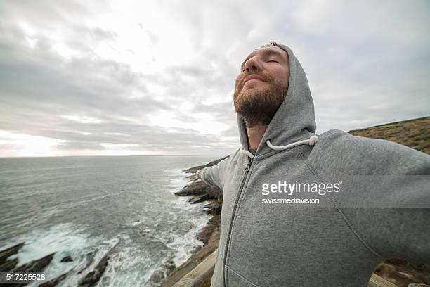 Allegro giovane uomo si rilassa sul mare