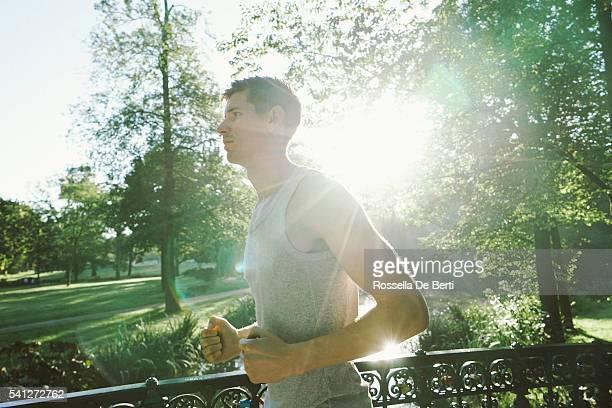 Joyeuse jeune homme courir en extérieur à l'aube