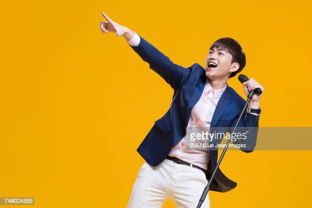 Cheerful young man singing with microphone
