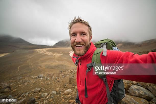 Cheerful young man takes selfie portrait on Tongariro Alpine Crossing