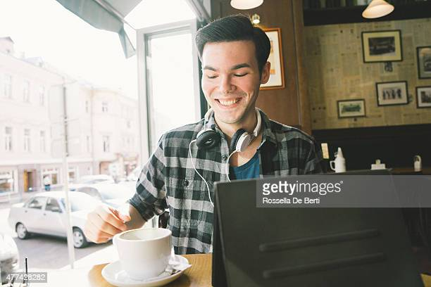 Cheerful Young Man Using Tablet In Coffee Shop