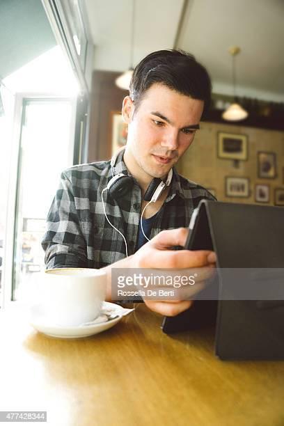 Allegro giovane uomo utilizzando Tablet In caffetteria