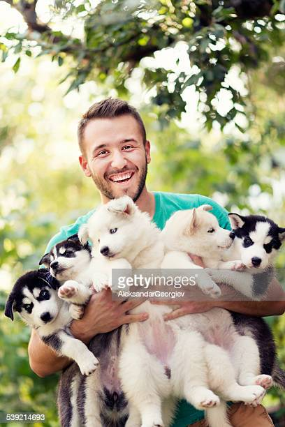 Cheerful Young Men Holding Five Lovely Husky Baby Puppies