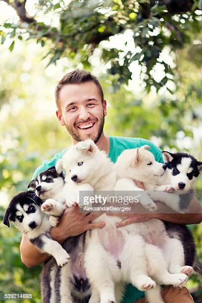 Joyeux jeunes hommes tenant cinq charmants Husky bébé grillée