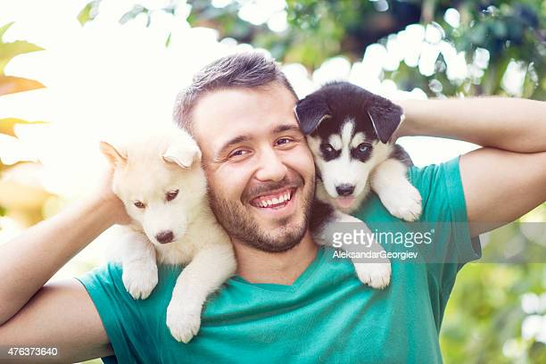 Cheerful Young Men Holding Two Lovely Husky Baby Puppies