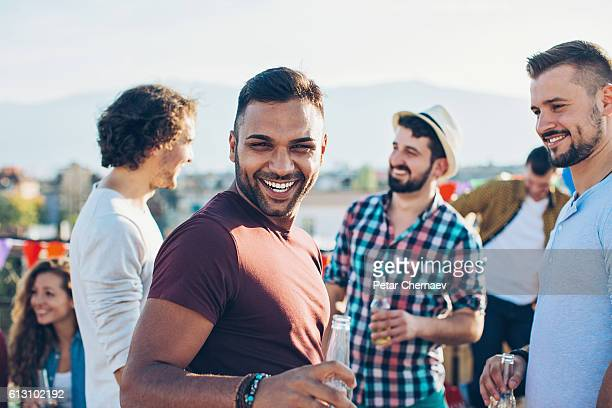 Cheerful young men on a rooftop party
