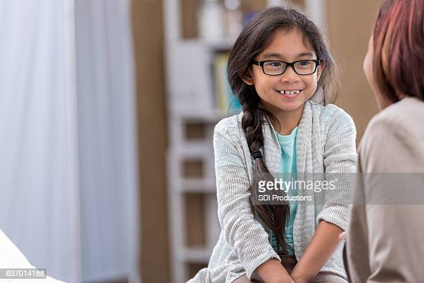 Cheerful young patient talks with pediatrician