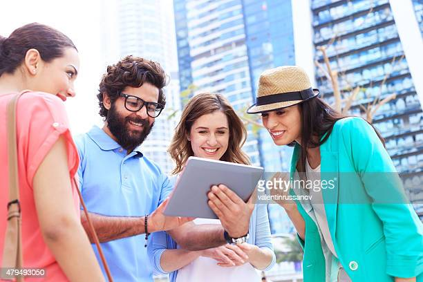 Cheerful young people in the city with digital tablet.